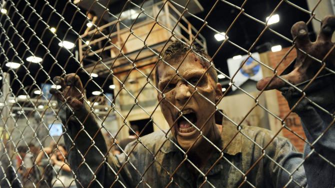 """A zombie character in an exhibit inspired by the television series """"The Walking Dead"""" screams at onlookers during the Preview Night event on Day 1 of the 2013 Comic-Con International Convention on Wednesday, July 17, 2013 in San Diego, Calif. (Photo by Chris Pizzello/Invision/AP)"""