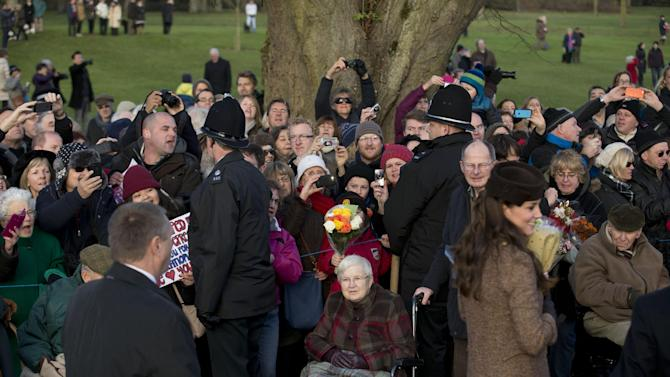 A man, stood left of the police officer at left, shouts a protest comment from the crowd as Kate the Duchess of Cambridge, at right, leaves and speaks to people gathered outside after attending the British royal family's traditional Christmas Day church service at St. Mary Magdalene Church in Sandringham, England, Thursday, Dec. 25, 2014.  (AP Photo/Matt Dunham)