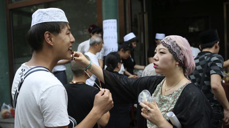 A Muslim woman feeds a man lamb kebab as they celebrate Eid al-Fitr near the Niujie mosque in Beijing