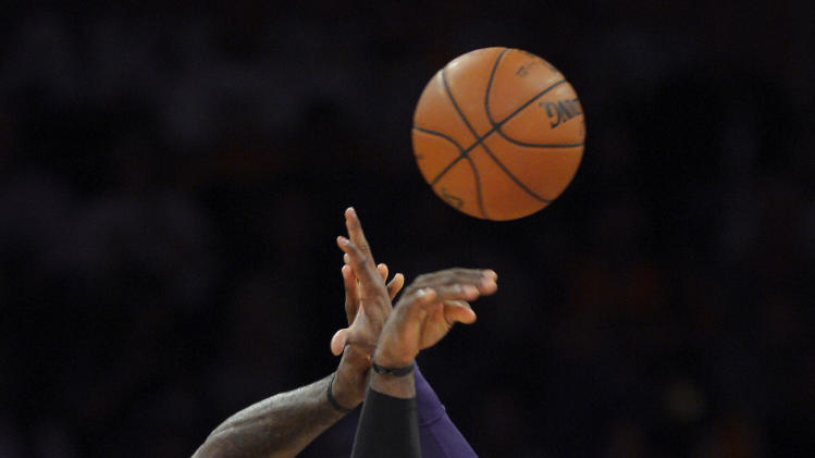 Miami Heat forward LeBron James (6) passes over Los Angeles Lakers guard Kobe Bryant during the first half of their NBA basketball game, Thursday, Jan. 17, 2013, in Los Angeles. (AP Photo/Mark J. Terrill)
