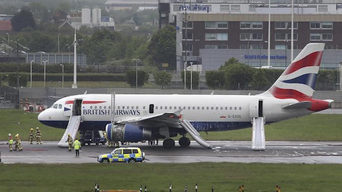 Emergency services attend a British Airways passenger plane after it had to make an emergency landing at Heathrow airport. early Friday May 24, 2013. Both runways at Heathrow airport were closed after a British Airways plane had to make an emergency landing, and Heathrow said that all passengers and crew had been safely evacuated from the plane following the incident. Footage broadcast on British television shows the plane in the air with smoke streaming from one engine. (AP Photo/Steve Parsons, PA) UNITED KINGDOM OUT - NO SALES - NO ARCHIVES