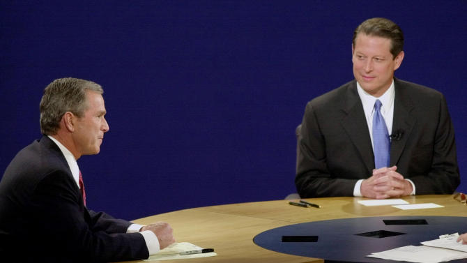 "FILE - In this Oct. 11, 2000 file photo, Democratic presidential candidate, Vice President Al Gore, right, and Republican presidential candidate Texas Gov. George W. Bush wait for the start of a debate, at Wait Chapel at Wake Forest University in Winston-Salem, N.C. In presidential politics, everybody's searching for ""the moment."" The campaigns don't know when or how it will come, but they watch for something _ awkward words or an embarrassing image _ that can break through and become the defining symbol of the other guy's flaws. Now all eyes are on the series of three presidential debates that starts Wednesday. (AP Photo/David Phillip)"