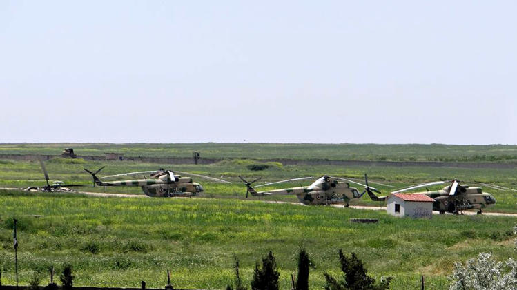FILE - In this June 18, 2013 file photo, citizen journalism image provided by Aleppo Media Center AMC which has been authenticated based on its contents and other AP reporting, shows Syrian military helicopters at Mannagh air base in Aleppo province, Syria. Syrian rebels captured a major air base in the north of the country on Tuesday after months of fighting, depriving President Bashar Assad's forces of one of their main posts near the border with Turkey, activists said. State TV denied that the base had fully fallen. (AP Photo/Aleppo Media Center AMC, File)