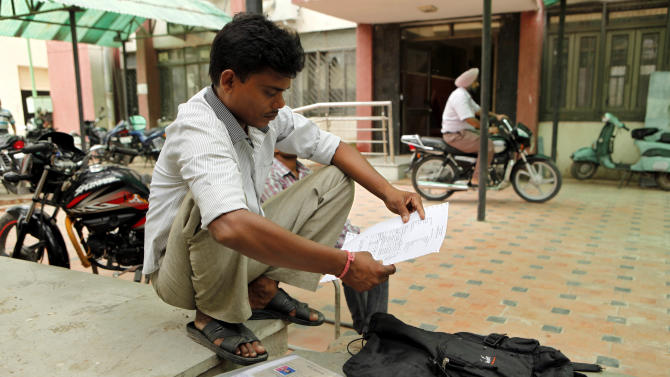 In this photo taken Wednesday, Aug. 29, 2012, an Indian man Vijay Kumar looks at his certificates outside an employment exchange office in New Delhi, India. Thousands of unemployed like Kumar flock to 900 state-run job centers across the country, where they hope to get what many in this country believe is the ticket to a better life, a government job. While millions of job seekers have impressive sounding diplomas, many don't have the skills promised by those certificates from colleges and technical institutes with poor standards. (AP Photo/Rajesh Kumar Singh)