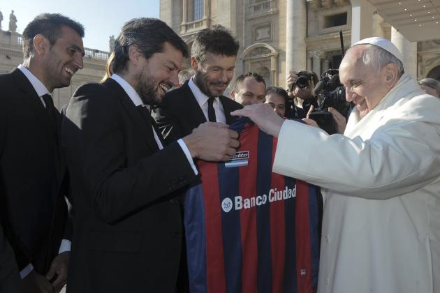 Pope Francis holds a jersey of Argentine soccer team San Lorenzo during the Wednesday general audience at the Vatican