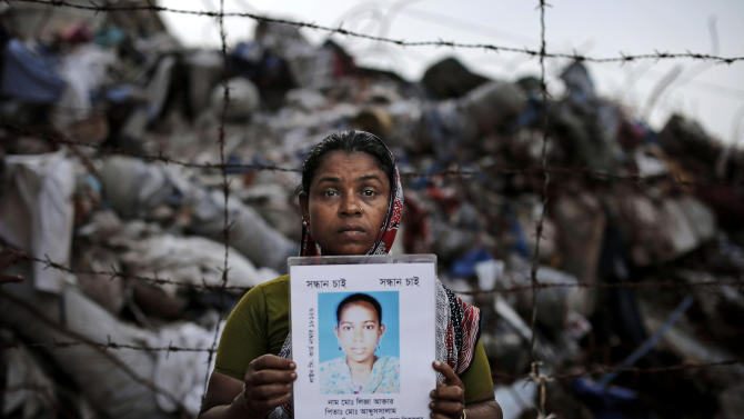 In this picture taken Friday, June 14, 2013, Bangladeshi Jahanana Begum holds a picture of her daughter Liza Aktar, who was a garment worker and is missing following the collapse of the Rana Plaza building as she poses next to the rubble in Savar, near Dhaka, Bangladesh. The deadliest disaster in the history of the garment industry killed 1,129 people, but hundreds more are still missing almost three months after the collapse. (AP Photo/Kevin Frayer)