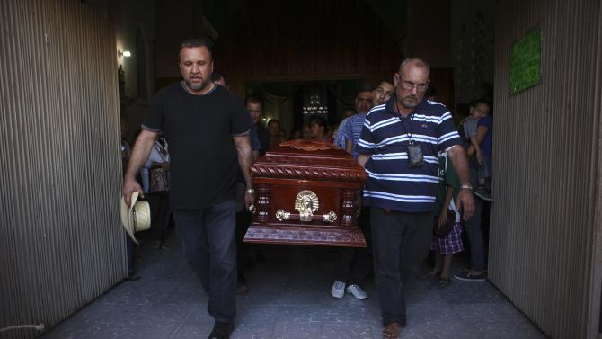 Vigilante leader Mora carries the coffin containing the body of his slain son who died in a shootout between rival vigilantes, during his wake in the town of La Ruana