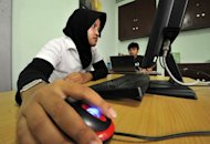 An Indonesian Muslim woman surfs the web in 2009. YouTube has begun restricting access to videos of an anti-Islamic film in the world&#39;s most populous Muslim nation, a government official said Sunday