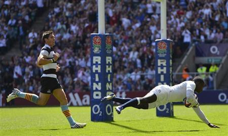 Wade of England scores a try as Hook of Barbarians watches during their international rugby union friendly match in London