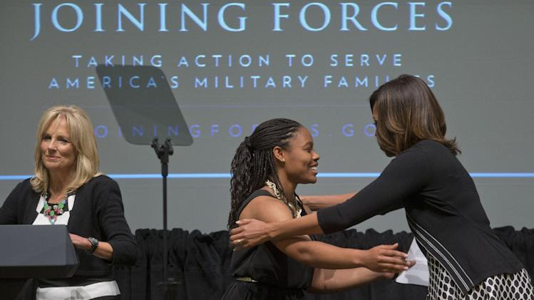 First lady Michelle Obama, right, hugs Chrissandra Jackson, center, accompanied by Dr. Jill Biden, left, at the third anniversary of Joining Forces, Wednesday, April 30, 2014, at the American Red Cross Hall of Service in Washington. Mrs. Obama announced pledges in excess of $150 million from foundations and corporations to help veterans and their families get the services they need in the places where they live as the country adjusts to a postwar footing. Jackson is a daughter of a military family. (AP Photo)