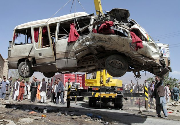 A damaged bus which was hit by a remote control bomb is lifted by a crane on the outskirts of Kabul, Afghanistan, Tuesday, Aug. 7, 2012. A militant detonated a remote-control bomb Tuesday morning, kil