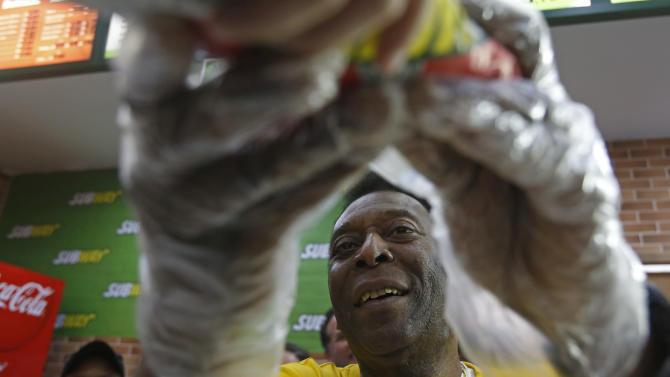 SUBWAY Global Ambassador and Brazilian soccer legend Pele, serves a sandwich to a lucky customer at a SUBWAY restaurant in Rio de Janeiro, Brazil on Saturday, July 12, 2014. (Photo by Dado Galdieri/Invision for SUBWAY Restaurants/AP Images)
