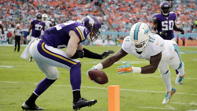 Miami Dolphins wide receiver Mike Wallace (11) scores a touchdown as Minnesota Vikings free safety Harrison Smith (22) is late with the tackle during the second half of an NFL football game, Sunday, Dec. 21, 2014, in Miami Gardens, Fla. (AP Photo/Lynne Sladky)