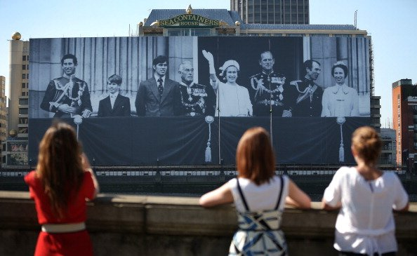 MAY 25: Poeple watch as a giant photograph of The British Royal family is installed on a building on The River Thames on May 25, 2012 in London, England. Erected to celebrate Queen Elizabeth II's Diam