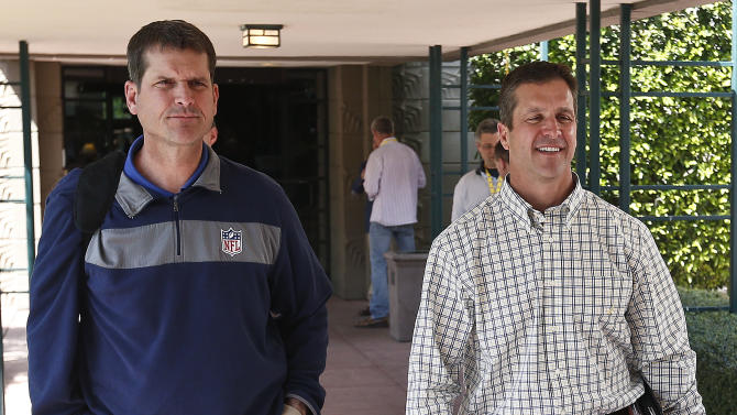 San Francisco 49ers coach Jim Harbaugh, left, walks with his brother John Harbaugh, coach of the Baltimore Ravens, at the NFL football annual meetings Tuesday, March 19, 2013, in Phoenix. (AP Photo/Ross D. Franklin)