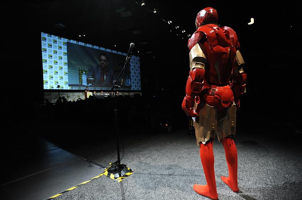 "A fan in an Iron Man costume asks a question of the cast at the ""Iron Man 3"" panel 2012 Comic Con on Saturday, July 14, 2012 in San Diego, Calif. (Photo by Jordan Strauss/Invision/AP)"