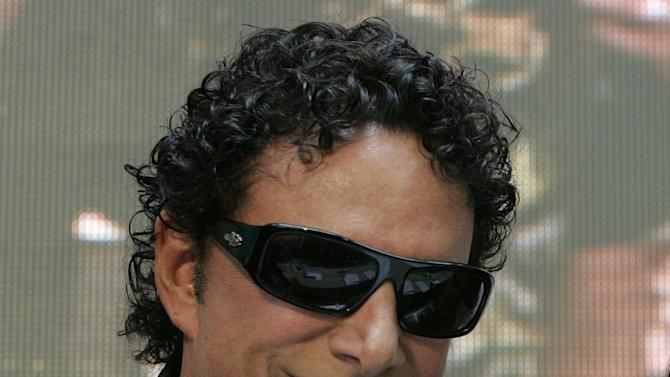 """FILE - In this March 2, 2009 file photo, Neal Schon poses for a photograph during a news conference at a mall in suburban Quezon City, north of Manila, Philippines.  Schon, the lead guitarist for the rock band Journey has filed a federal lawsuit in Minneapolis that accuses his former mother-in-law of libeling him in her blog posts. Schon says Judy Kozan, the former mayor of Waseca, has """"attacked and harassed"""" him for years through Internet postings and comments in the media. Schon's lawsuit says Kozan suggested that he has failed to support his ex-wife and their two daughters. (AP Photo/Aaron Favila)"""