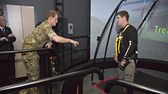 Wearing his British Army uniform, Britain's Prince Harry, left, visits with Corey Harmon and other wounded warriors undergoing physical therapy at the Computer Assisted Rehab Environment at Walter Reed National Military Medical Center in Bethesda, Md., just outside Washington, Friday, May 10, 2013. (AP Photo/J. Scott Applewhite, Pool)