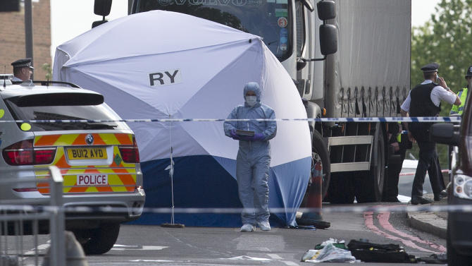 Police and forensic officers work near the scene of an attack in which two men are accused of butchering a British soldier near Woolwich barracks in London, Wednesday, May, 22, 2013.  Scotland Yard said officers responded to reports of an assault Wednesday afternoon in the London neighborhood of Woolwich. London Ambulance service said one man was found dead at the scene and two other men were taken to the hospital, with one in serious condition. (AP Photo/Alastair Grant)