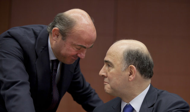 Spain's Economy Minister Luis de Guindos, left, speaks with French Finance Minister Pierre Moscovici during a meeting of  eurogroup finance ministers in Brussels on Monday, March 4, 2013. The eurogrou
