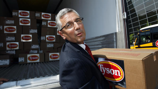Donnie Smith, CEO and president of Tyson Foods Inc., removes a box of frozen chicken drumstick stands, Thursday, June 21, 2012, in Jackson, Miss. Smith was participating in a new program with the National Urban League that is designed to reduce hunger in Mississippi, one of the poorest states in the nation. (AP Photo/Rogelio V. Solis)