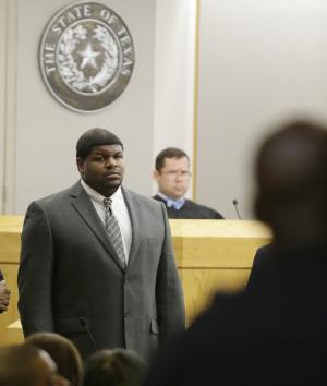 Former Dallas Cowboys' Josh Brent stands in court as potential jurors are directed into Judge Robert Burns, looking on in back, courtroom Friday, Jan. 10, 2014, in Dallas. Jury selection continues for the upcoming trial of Brent, who's accused of killing a practice squad player in a drunken-driving wreck. Opening statements in the case are expected next week. (AP Photo/LM Otero)