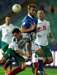 Italy's Daniele De Rossi (C) fights for the ball with Bulgaria's Georgi Milanov (L) during their World Cup 2014 qualification match at Vassil Levski stadium in Sofia. The match ended in a 2-2 draw