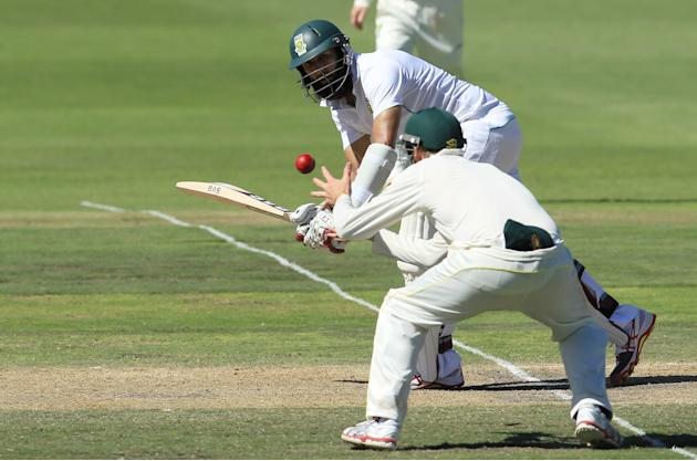 South Africa's batsman Hashim Amla, top, watches as Australia's fielder Steven Smith, bottom, fields off his shot on the third day of their 2nd cricket test match at St George's Park in Po