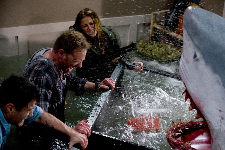 "In this image released by Syfy, Ian Ziering, second left, and Cassie Scerbo battle a shark in the Syfy original film ""Sharknado."" The network is announcing a sequel to ""Sharknado,"" which became an instant campy classic with its recent airing. The new film premieres in 2014. (AP Photo/Syfy)"