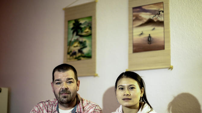 In this picture taken Tuesday, Feb. 11, 2014, Michael Guhle and his wife Thi An Nguyen from Vietnam sit in their apartment at the Weissensee district in Berlin, Germany. Guhle met the love of his life on the beach of a little fishing village in Vietnam. Nguyen was selling freshly cooked mussels and fruit to the German tourist and they immediately clicked. Soon the Berlin nursing home worker was saving up all of his money and vacation days to visit her. Marriage was supposed to bring them together. Instead, it was the beginning of a long ordeal apart. Germany blocked her from entering the country after she flunked the language test that Germany requires aspiring immigrants to pass - even those married to Germans. (AP Photo/Markus Schreiber)