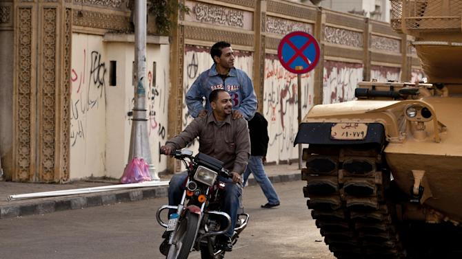 "Egyptians on a motorbike pass a tank staged outside the presidential palace as protesters opposed to Egyptian President Mohammed Morsi gather in Cairo, Egypt, Saturday, Dec. 8, 2012. Egypt's military said Saturday that serious dialogue is the ""best and only"" way to overcome the nation's deepening conflict over a disputed draft constitution hurriedly adopted by Islamist allies of President Mohammed Morsi, and recent decrees granting himself near-absolute powers. (AP Photo/Maya Alleruzzo)"