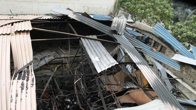 """The destroyed roof of the building is seen after Monday's explosion in downtown Nairobi, Tuesday, May 29, 2012. An explosion ripped through a building full of small shops in downtown Nairobi, injuring at least 33 people, including a woman who blamed the blast on a """"bearded man"""" who left behind a bag shortly before the detonation. (AP Photo/Sayyid Azim)"""