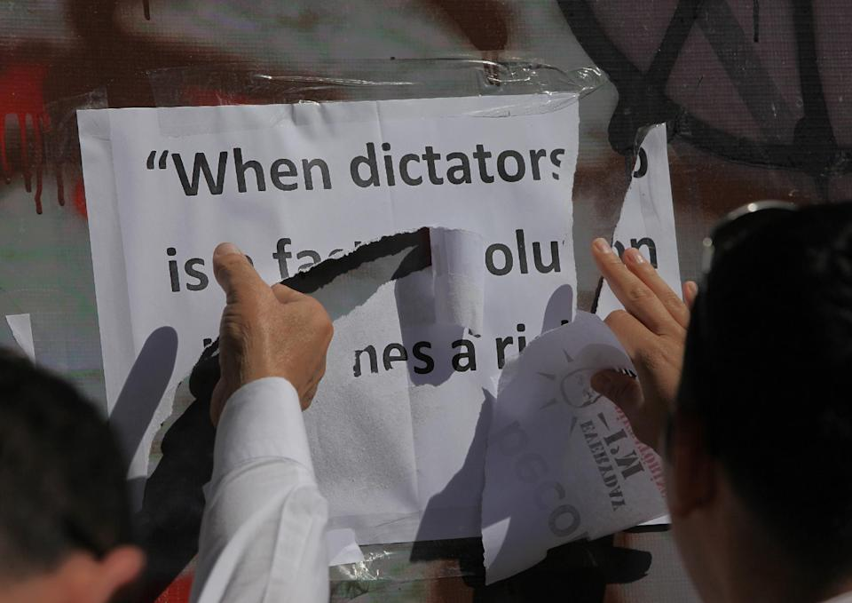 "Plaincloth police officers remove the words of French writer Victor Hugo, "" when dictatorship is a fact, revolution becomes a right"", placed on a monument by Turkish protesters, who were sitting in Kugulu Park in Ankara, Turkey, Thursday, June 13, 2013. (AP Photo/Burhan Ozbilici)"
