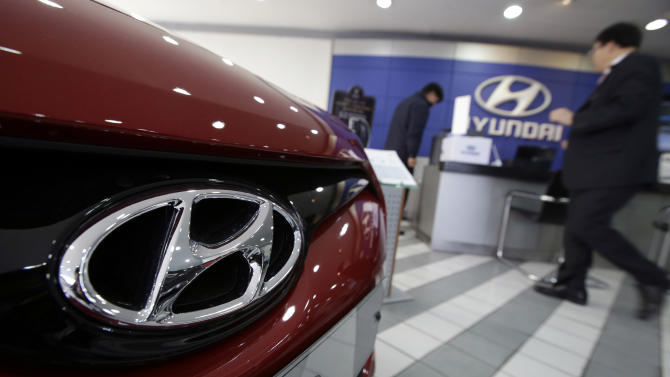 FILE - In this Jan. 23, 2014 file photo, the logo of Hyundai Motor Co. is seen on a car at the automaker's showroom in Seoul, South Korea. Hyundai Motor Co. said Thursday, Oct. 23, 2014, its profit sank nearly 30 percent for the July-September quarter, hurt by a stronger South Korean currency and weak sales growth in its home market. (AP Photo/Lee Jin-man, File)