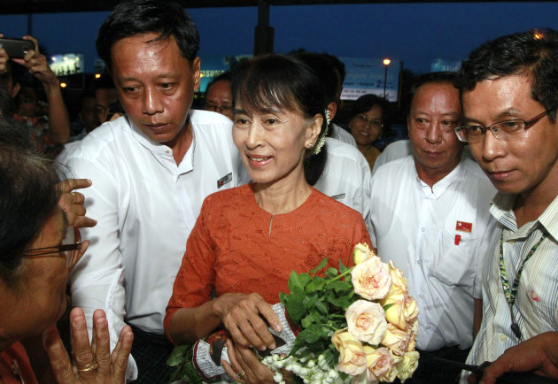 Myanmar opposition leader Aung San Suu Kyi, center, is greeted by a supporter upon her arrival at Yangon International Airport in Yangon, Myanmar, to leave for Bangkok, Thailand, on Tuesday, May 29, 2