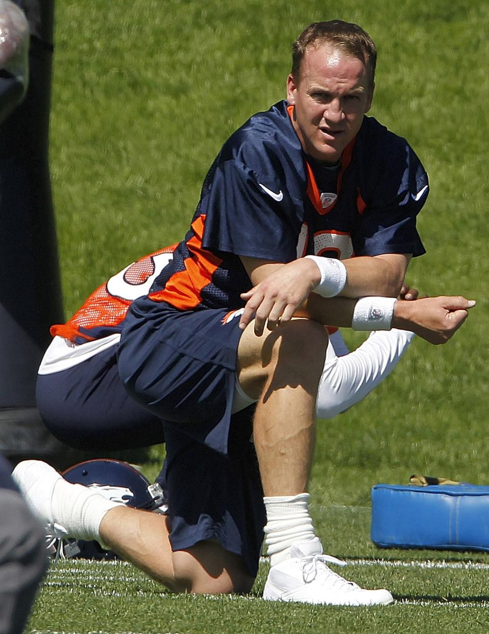 Denver Broncos quarterback Peyton Manning takes a knee during stretching at minicamp at the NFL team's football training facility in Englewood, Colo., on Monday, May 21, 2012.  (AP Photo/Ed Andrieski)
