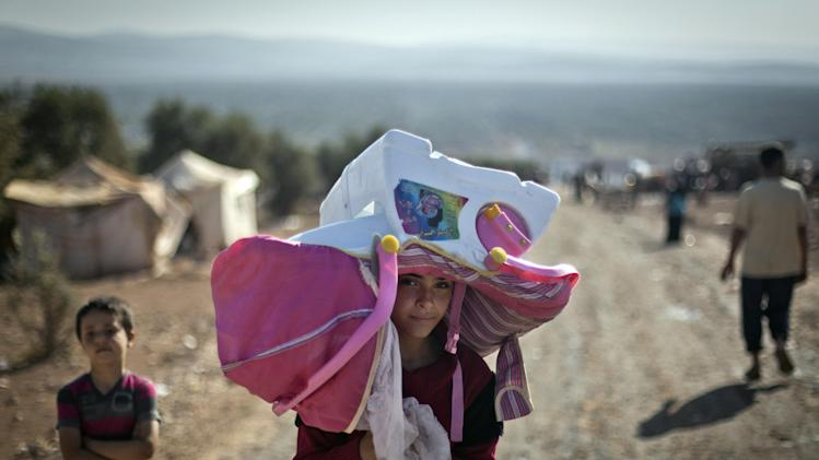 FILE - In this Wednesday, Nov. 7, 2012 file photo, a Syrian girl who fled with her family from the violence in their village carries a baby seat over her head at a camp in the Syrian village of Atmeh, near the Turkish border with Syria. Most of the displaced people in the tent camp rising near this village on the Syrian-Turkish border are children. All have fled the violence of Syria's civil war further south. Many have seen violence themselves, some have lost relatives, and most have trouble sleeping and panic when they hear loud noises or airplanes, their parents say. The Atmeh camp was born of necessity about three months ago, say the local rebels who run the place, distributing tents and food aid provided by a smattering of aid organizations.(AP Photo/ Khalil Hamra, File)