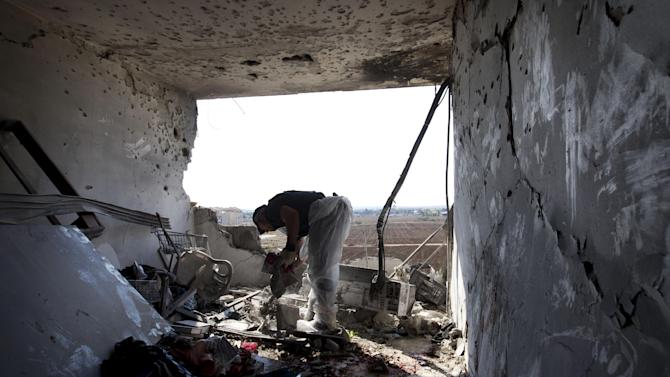 A Zaka volunteer cleans blood stains from an apartment in a building that was hit by a rocket fired from the Gaza Strip, where three people were killed in Kiryat Malachi, southern Israel, Kiryat Malachi, southern Israel,Thursday, Nov. 15, 2012. Militants in the Hamas-ruled Gaza Strip killed three Israelis on Thursday in a rocket attack liable to deepen a bruising Israeli air, naval and artillery offensive against Palestinian rocket squads. The casualties were the first in Israel since it launched its operation on Wednesday with the assassination of Hamas' top military commander. (AP Photo/Ariel Schalit)