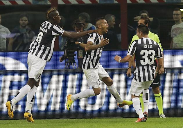 Juventus midfielder Arturo Vidal, of Chile, center, jumps in celebration after scoring while teammates Juventus midfielder Paul Pogba, of France,  left, and Juventus midfielder Mauricio Isla, of Chile