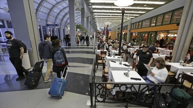 In this photo taken Tuesday, Dec. 18, 2012, at O'Hare International Airport in Chicago, a diner at Wolfgang Puck Cafe sits in a sidewalk cafe setting in Terminal 3. Getting stranded at an airport once meant camping on the floor and enduring hours of boredom in a kind of travel purgatory with nothing to eat but fast food. Tough economic times are helping drive airports to make amends and transform terminals with a bit of bliss: spas, yoga studios, luxury shopping and restaurant menus crafted by celebrity chefs. (AP Photo/M. Spencer Green)