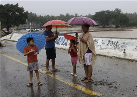Members of a family stand with umbrellas on a bridge that was damaged by last month's Hurricane Manuel, during rain brought on by Hurricane Raymond in Coyuca de Benitez