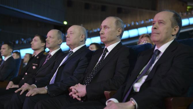 Russia's Federal Security Service Director Bortnikov, President Putin and Head of the Foreign Intelligence Service Fradkov sit during a concert honouring past and present security service staff at the State Kremlin Palace in Moscow