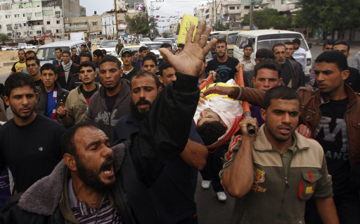 Mourners carry the body of Palestinian Matar Abu Ata, 20, killed in a recent Israeli strike, during his funeral in Gaza City, Sunday, Nov. 11, 2012. While cross-border fighting is a common occurrence, hostilities spiraled sharply over the weekend, with bombardments from Gaza causing rare Israeli casualties and Israeli strikes killing at least six Palestinians. (AP Photo/Hatem Moussa)
