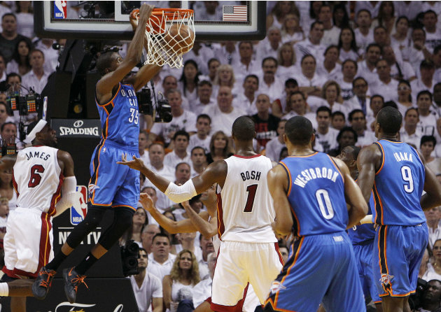 Oklahoma City Thunder small forward Kevin Durant (35) dunks as Miami Heat small forward LeBron James (6) defends during the first half at Game 5 of the NBA finals basketball series, Thursday, June 21,