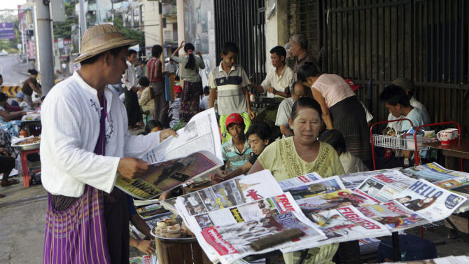 FILE - In this June 10, 2012 file photo, a man buys a weekly news journal at a roadside newspaper stand in Yangon, Myanmar. Myanmar will allow private daily newspapers starting in April for the first time since 1964, the government said Friday, Dec. 28, 2012 in the latest step toward allowing freedom of expression in the long-repressed nation. (AP Photo/Khin Maung Win, File)