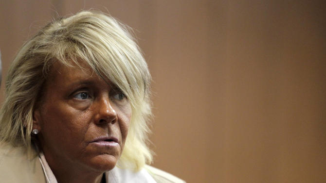 """FILE - In this May 2, 2012 file photo, Patricia Krentcil, 44, waits to be arraigned at the Essex County Superior Court  in Newark, N.J., where she appeared on charges of endangering her 5-year-old child by taking her into a tanning salon. Connecticut novelty company HeroBuilders is selling a """"tanorexic"""" action figure based on Krentcil. (AP Photo/Julio Cortez, File)"""