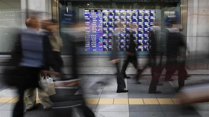 Passers-by walk past a stock quotation board outside a brokerage in Tokyo December 4, 2013. REUTERS/Toru Hanai/files