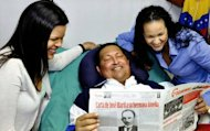 Venezuelas' VTV shows President Hugo Chavez, surrounded by his daughters and holding an issue of Granma, Cuba's official newspaper, at hospital in Havana on February 15, 2013
