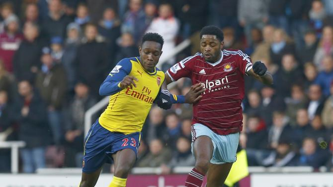 Arsenal's Danny Welbeck is challenged by West Ham United's Alex Song during their English Premier League soccer match at Upton Park in London