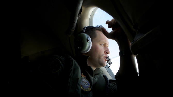 In this Monday, March 24, 2014 photo, a crew member of an Royal Australian Air Force AP-3C Orion patrol plane, looks out of his observation window whilst searching for the missing Malaysia Airlines Flight MH370 over the Indian Ocean. They lean forward as far as they can, occasionally pressing their foreheads against the plane's windows so hard they leave grease marks, staring out at a punishingly unbroken expanse of gray water that seems, at times, to blend into the clouds. Their eyes dart up and down, left and right, looking for something - anything - that could explain the fate of the missing Malaysia Airlines plane. (AP Photo/Richard Wainwright, Pool, File)